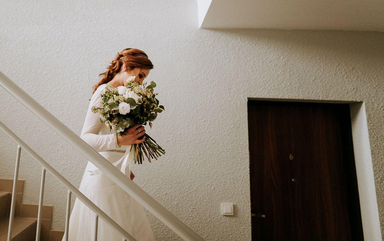 pani mloda schodzi po schodach trzymajac w rece bukiet slubny
