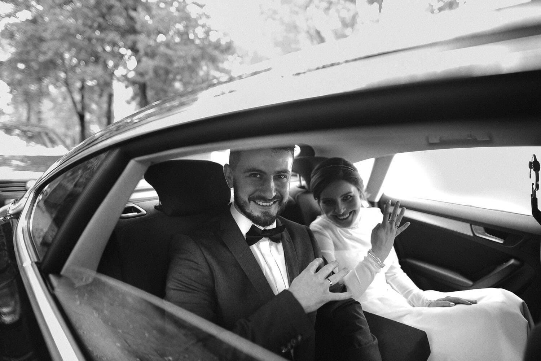 panstwo mlodzi siedza w samochodzie i pokazuja obraczki